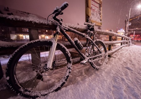 end of biking season.parked bicycle covered by snow from a heavy snowstorm.Winter cycling Imagens - 110720367