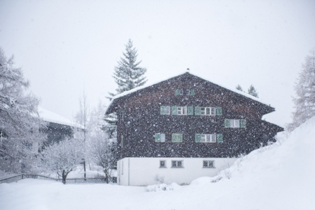 beautiful winter landscape with a mountain house in snowstorm