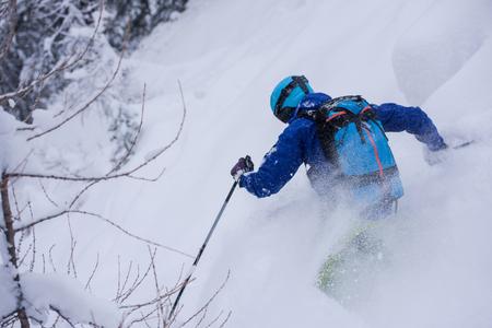 freeride skier with rucksack skiing downhill on fresh powder snow Stok Fotoğraf