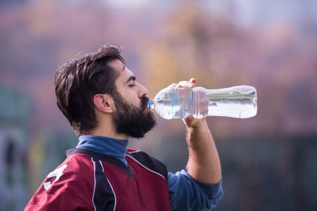 A tired american football player drinking water while resting after hard training at field