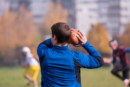 Team coach throwing the ball into the group of young american football players in action during the training at the field Stock Photo