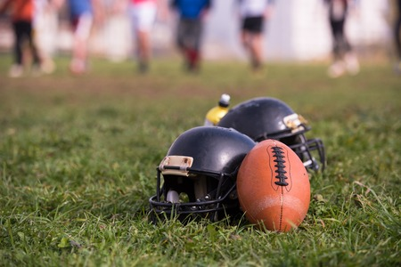 American football helmets and ball lying on field