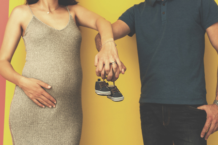 young  pregnant couple holding newborn baby shoes isolated on yellow background,family and parenthood concept