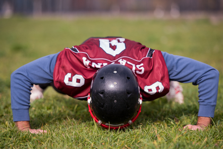 american football player doing push ups during training at the field