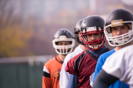 portrait of young american football team standing one behind the other on field Stock Photo