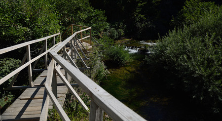 Red wooden bridge over wild river in beautiful nature in summer Standard-Bild - 111175417