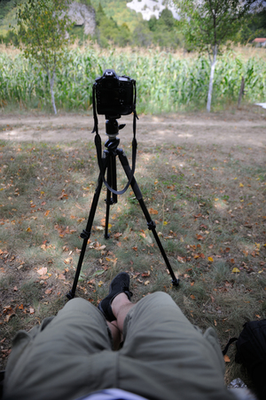 Pov photographer in nature taking time lapse photo on pro dslr camera with tripod while sitting in chair and relaxing