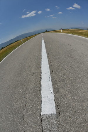 Country road asphalt lines with beautiful nature and sunny summer day with blue sky