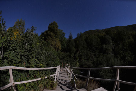 Wooden old bridge in forest over treetops and wild river in dark night with stars and milky way in sky