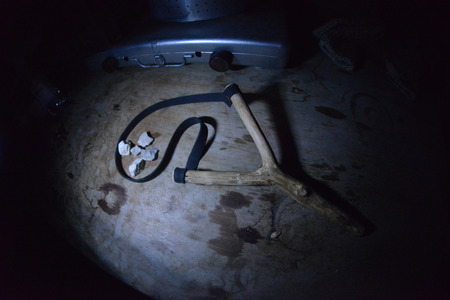 Slingshot weapon toy in dark on wooden  table Stock Photo
