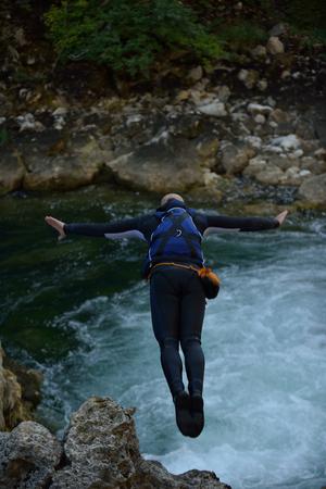 Man jumping in wild river adrenalin sport canyoning