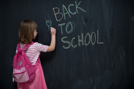 Happy school girl child with backpack writing  back to school on black chalkboard Banque d'images