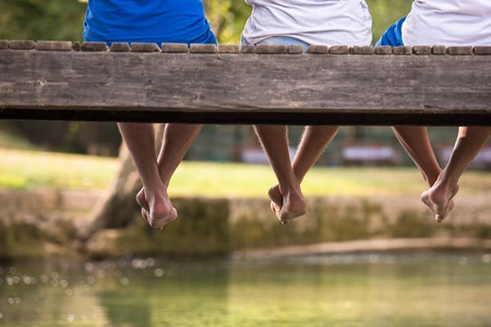 Group of  people sitting at wooden bridge over the river with a focus on hanging legs
