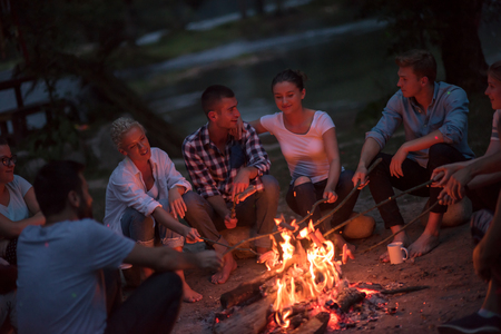 A group of happy young friends relaxing and enjoying  summer evening around campfire on the river bank Фото со стока