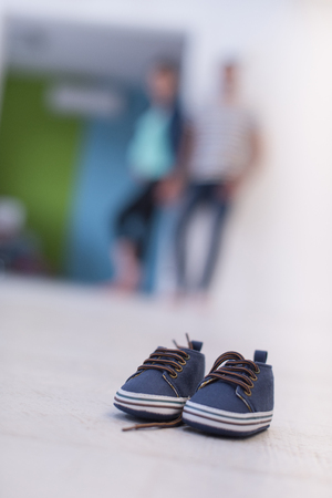 A little cute pair of blue baby shoes on a wooden floor with future parents Archivio Fotografico