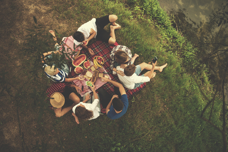 A group of young friends enjoying picnic time drink and food in beautiful nature on the river bank top view