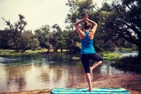Healthy woman relaxing while meditating and doing yoga exercise in the beautiful nature on the bank of the river