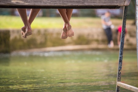 A group of  people sitting at wooden bridge over the river with a focus on hanging legs