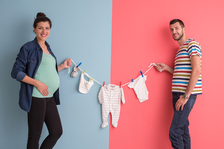 Beautiful pregnant woman and her husband expecting baby holding baby bodysuits and smiling over colorful