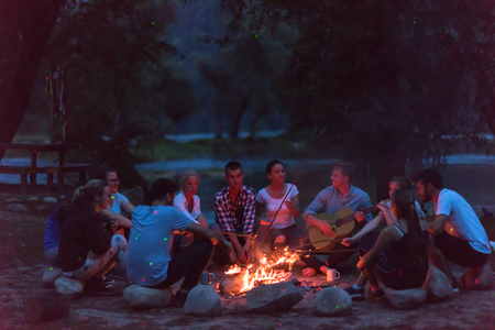 A group of happy young friends relaxing and enjoying  summer evening around campfire on the river bank Stock Photo