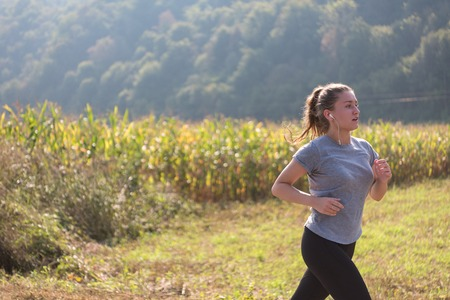 A young woman enjoying in a healthy lifestyle while jogging along a country road, exercise and fitness concept