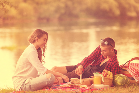 Couple in love enjoying picnic time drink and food in beautiful nature on the river bank Imagens
