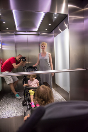young father taking pictures of his happy family in the mirror of the elevator