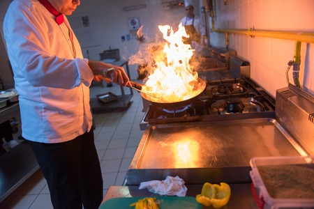 Chef cooking and doing flambe on food in restaurant kitchen Stok Fotoğraf