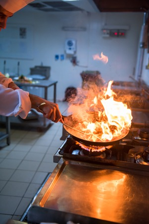 Chef cooking and doing flambe on food in restaurant kitchen Foto de archivo - 113689182