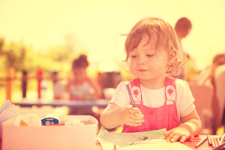 cute little girl cheerfully spending time using pencil crayons while drawing a colorful pictures in the outside playschool Фото со стока