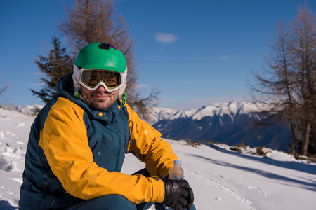 Snowboarder relaxing and posing at sunny day on winter season with blue sky