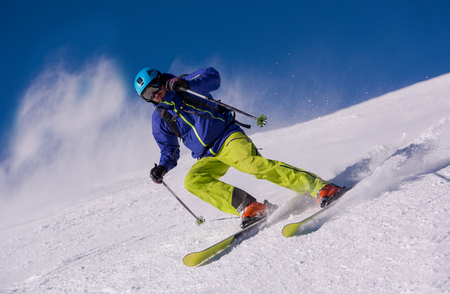 Young athlete freestyle Skier having fun while running downhill in beautiful Alpine landscape on sunny day during winter season Stock Photo