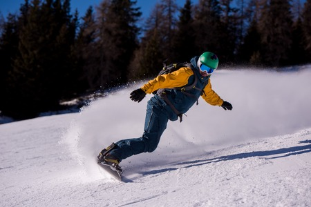 Young freestyle snowboarder running down the slope and ride free style at sunny winter day on Alpine mountains. Winter sport and recreation, leisure outdoor activities.