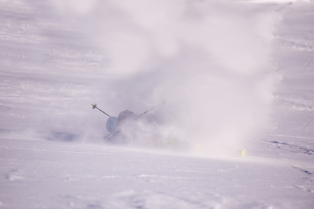 Freestyle snowboarder crashes while carving down snowy mountain and leaves a trail of snowflakes behind him
