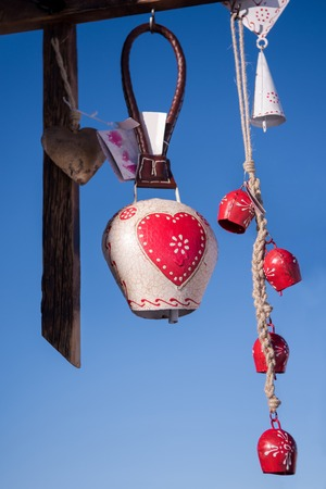 Traditional cow bells as home decoration or gift hanging on a wooden beam with blue sky