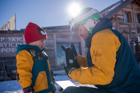 Young happy father preparing his little son for the first time on a snowboard during sunny winter day at beautiful  ski resort 스톡 콘텐츠