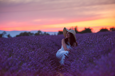 Woman portrait in lavender flower field in sunset and night time