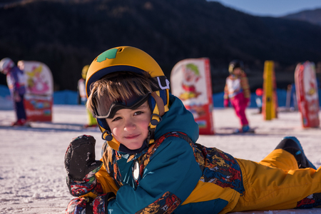 little boy snowboarder having fun while lying on the snow during the winter vacation at ski resort in sunny day