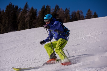 Young athlete freestyle Skier having fun while running downhill in beautiful Alpine landscape on sunny day during winter season 版權商用圖片