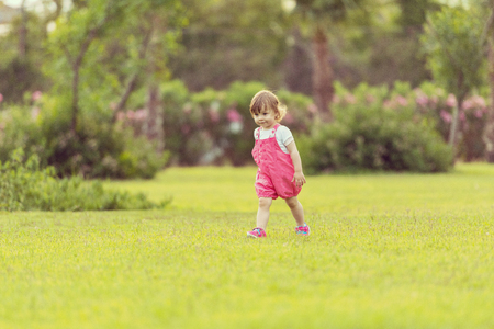 playful cute little girl cheerfully spending time while running in the spacious backyard on the grass Standard-Bild - 114262908