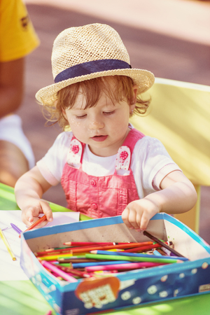 Cute little girl cheerfully spending time using pencil crayons while drawing a colorful pictures in the outside playschool Standard-Bild - 114266177