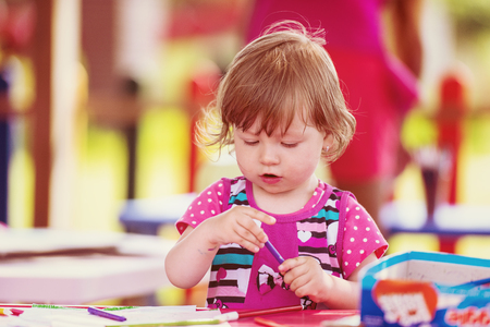 Cute little girl cheerfully spending time using pencil crayons while drawing a colorful pictures in the outside playschool