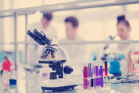Microscopio en el lugar de trabajo cerca de tubos de ensayo con diferentes líquidos. Concepto de salud y biotecnología Foto de archivo