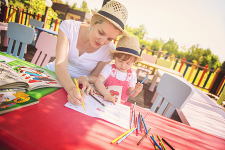 Young mother and her little daughter cheerfully spending time together using pencil crayons while drawing a colorful pictures in the outside playschool Фото со стока