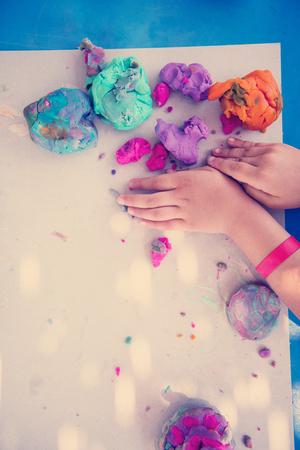 Vue de dessus des mains d'enfants jouant avec de l'argile colorée dans une aire de jeux extérieure Banque d'images