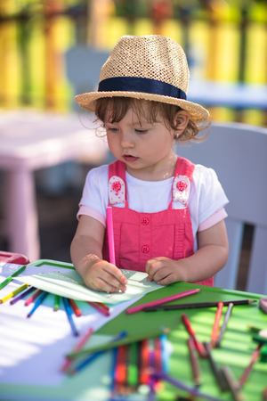 cute little girl cheerfully spending time using pencil crayons while drawing a colorful pictures in the outside playschool 写真素材