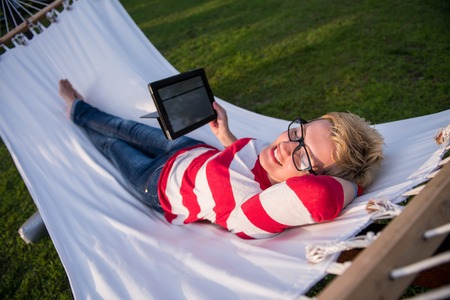 young woman using a tablet computer while relaxing on hammock in a peaceful garden during holiday