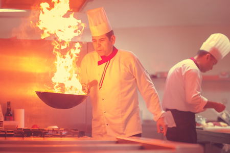 Chef cooking and doing flambe on food in restaurant kitchen 免版税图像