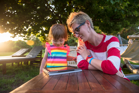 Happy mother and her little daughter enjoying free time using tablet computer while relaxing  on holiday home garden during sunny day Imagens