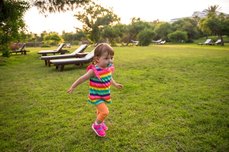 playful cute little girl cheerfully spending time while running in the spacious backyard on the grass